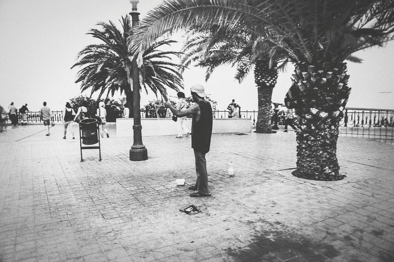 Street performer performing at the Port of Tarragona, Spain Palm Tree Tree Lifestyles Beach Outdoors Urbanphotography City Urban Streetphotography Landscapephotography Landscape Explore Beachphotography Port Beautifuldestinations Amazing View Travel Streetphoto Street Trees Streetperformer Streetperformance Artist Blackandwhite Bw_collection
