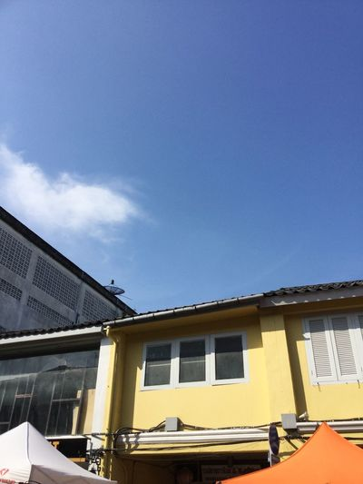 Yellow building with blue sky Yellow Building Built Structure Architecture Building Exterior Sky Building Day Nature Blue Window House Residential District Outdoors Cloud - Sky City Sunlight Copy Space Old No People Low Angle View