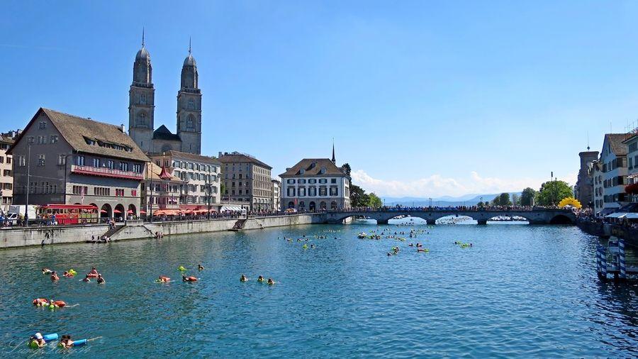 People enjoying in limmat river by buildings against blue sky