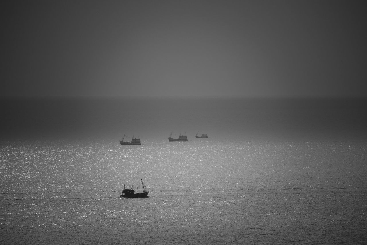 Silhouette Boats Sailing In Sea Against Clear Sky