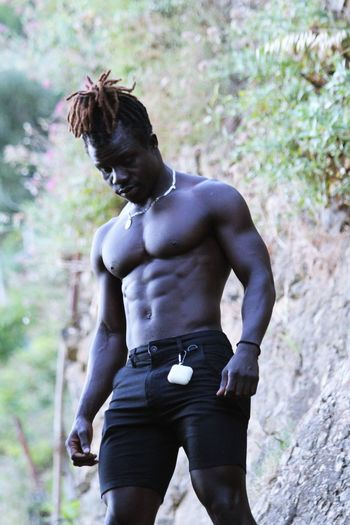 Full length of shirtless man standing on land