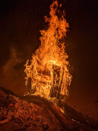 Bonfire on wooden log at night