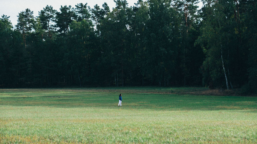 Man running on field in forest