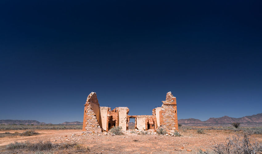 Old ruins of building on field against clear blue sky