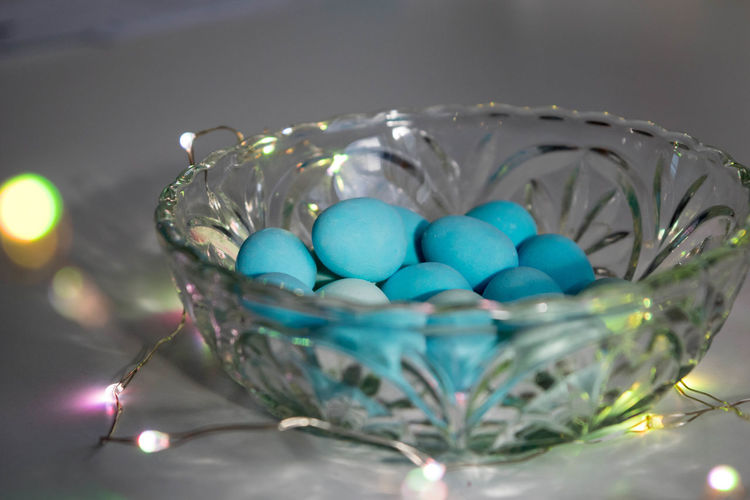 Close-up of easter eggs and illuminated lights in container on table
