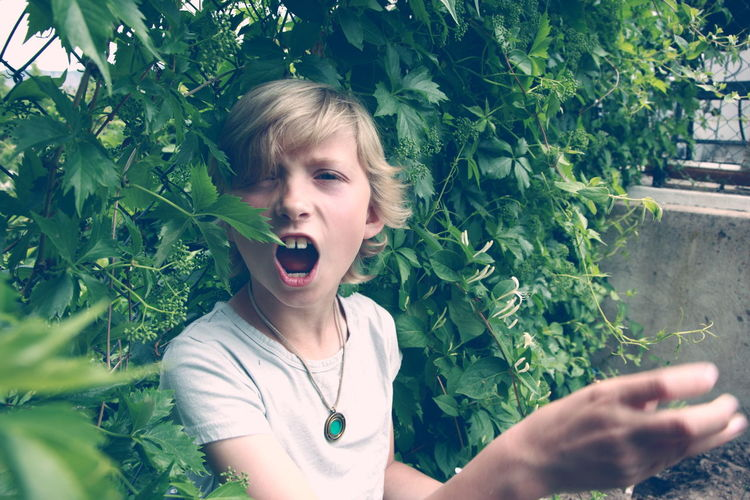 Close-Up Portrait Of Boy Against Plants