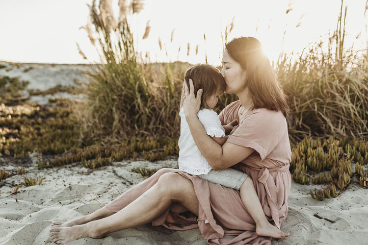Mother and daughter sitting on land