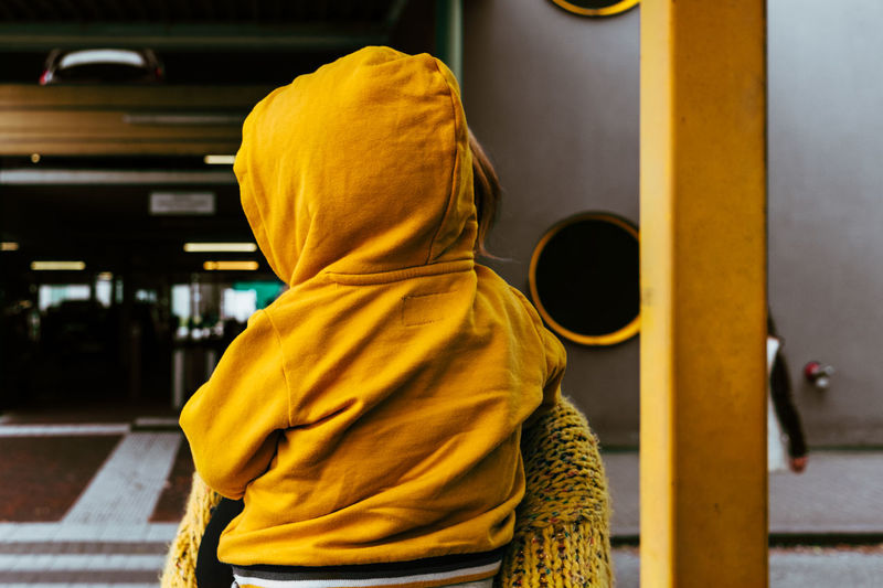 Close-up of woman carrying son wearing yellow hooded shirt