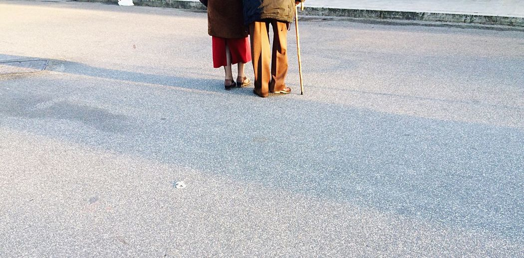 Low section of senior couple walking on street