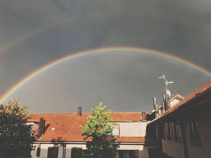 Rainbow over houses against sky