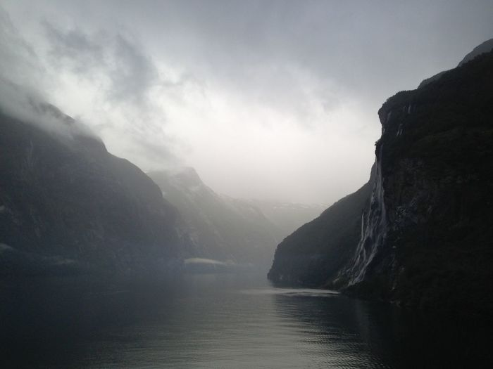Scenic view of river amidst mountains against sky during foggy weather
