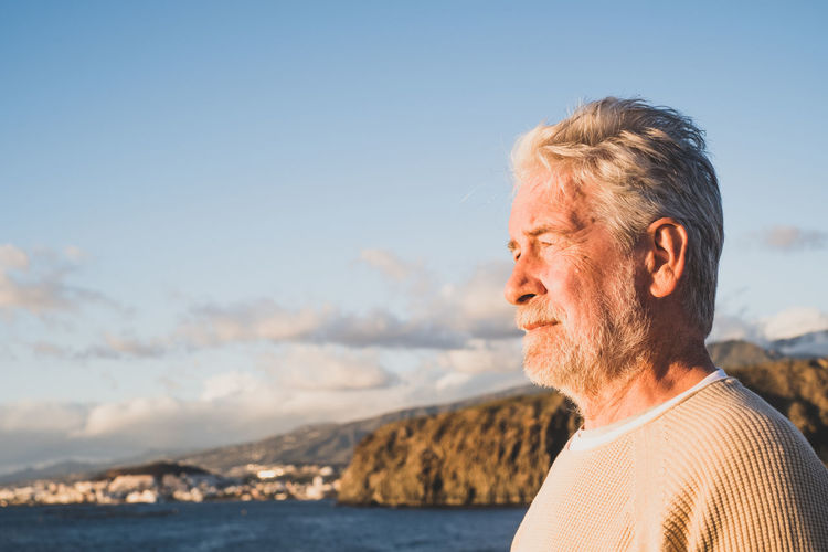 Senior man looking away at sea against sky during sunset