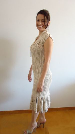 Portrait Of Smiling Woman In Dress Standing Against White Wall