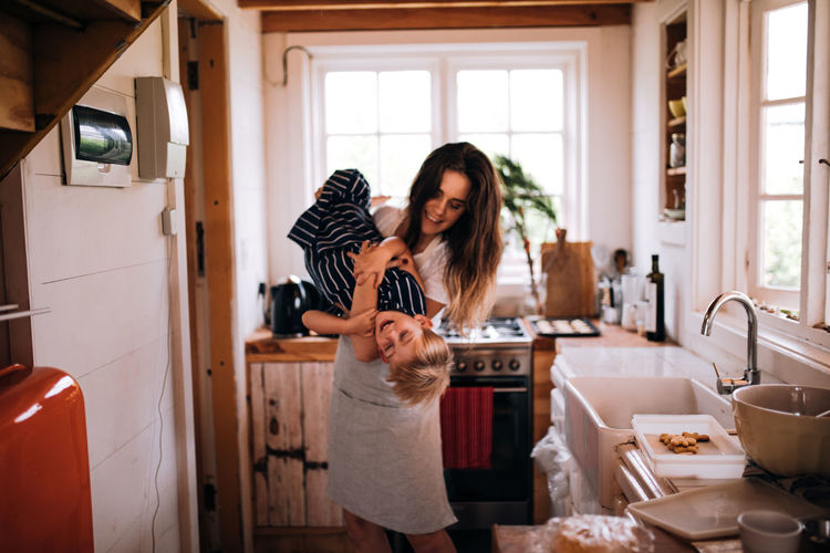 Mother playing with cute son in kitchen at home