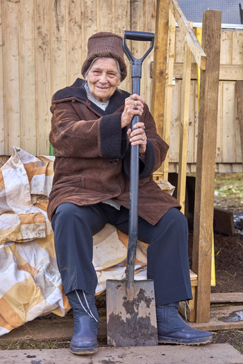Full Length Portrait Of Smiling Senior Woman With Spade Sitting In Backyard