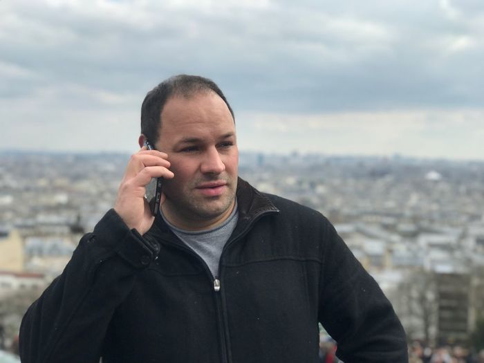 Man talking on phone while standing against cityscape