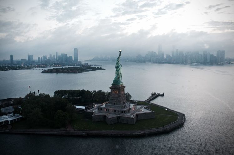 Statue of Liberty in New York Harbor shot from a Helicopter on a Grey, Early Morning with Financial District in the Background. Aerial Aerial Shot Aerial View America Architecture Building Exterior Built Structure City Cityscape Cloud - Sky Freedom Gotham Helicopter View  Immigration Liberty Liberty Island New York New York City New York Harbor Sculpture Sky Statue Statue Of Liberty Travel Water