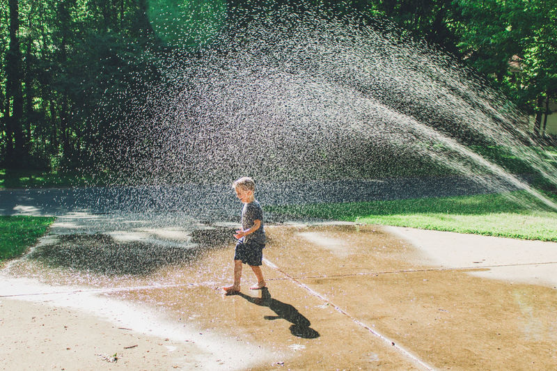 Boy playing in sprinkler water