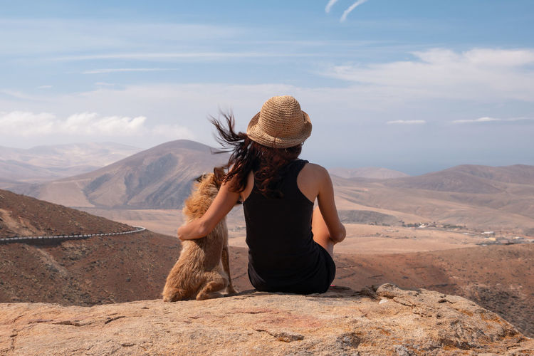 Rear view of woman with dog sitting on cliff against sky