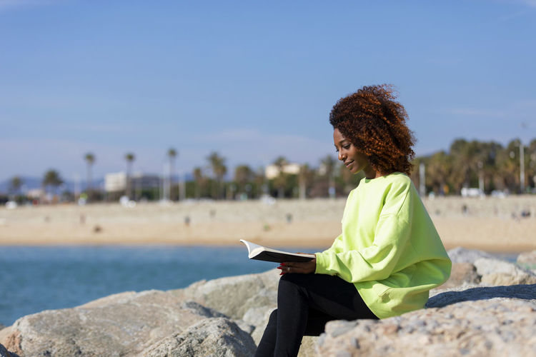 Side view of a young curly afro woman sitting on a breakwater holding a book while smiling and looking away outdoors One Person Young Adult Leisure Activity Sitting Real People Young Women Technology Focus On Foreground Casual Clothing Curly Hair Water Sky Lifestyles Connection Women Smiling Wireless Technology Hair Communication Hairstyle Woman African American Afro Denim Happiness Happy Fun Daylight Sunlight