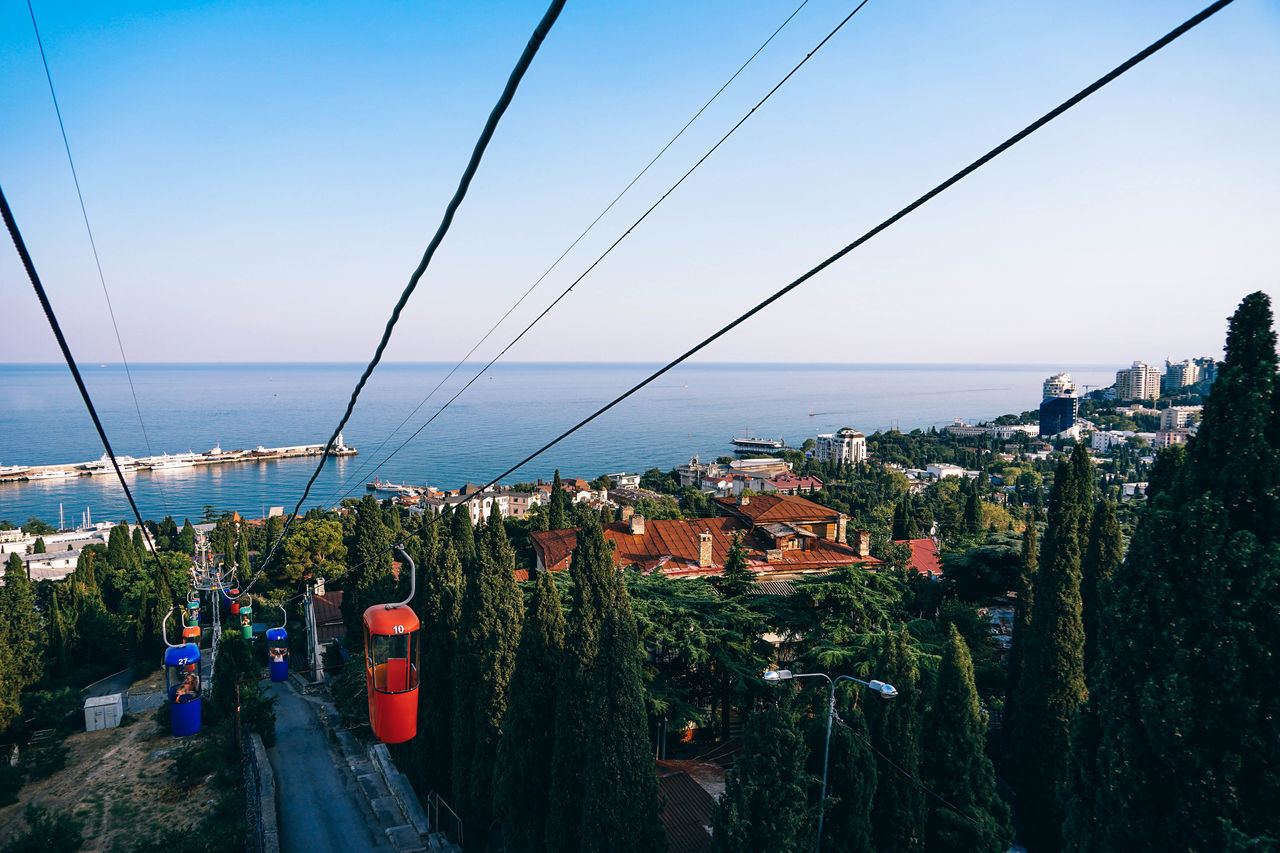 sea, horizon over water, architecture, built structure, building exterior, water, nature, outdoors, cable, day, sky, scenics, no people, beauty in nature, clear sky, tree, city, cityscape