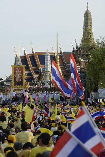 High angle view of people with thai flags at event outside temple