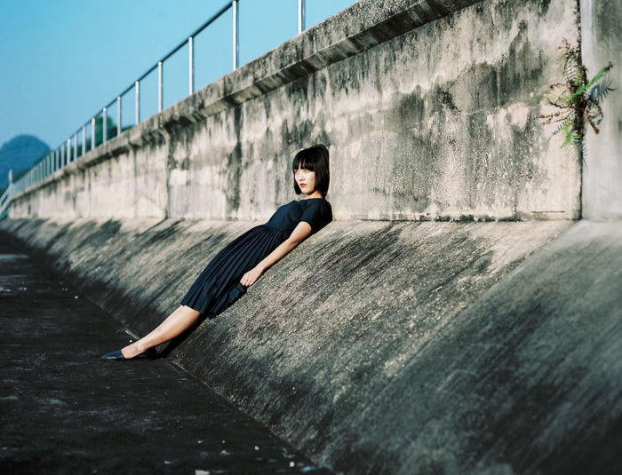 Full length of young woman leaning on wall