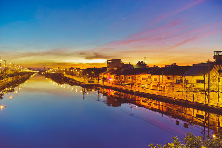 Illuminated houses reflecting on calm river against sky during sunset