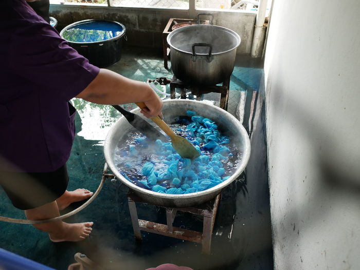 High angle view of man boiling textile