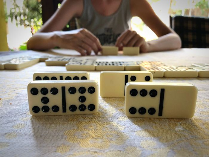 Midsection of woman playing domino on table