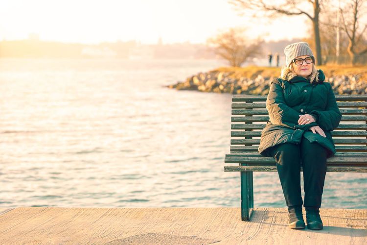Full length of woman sitting on bench against sea in winter