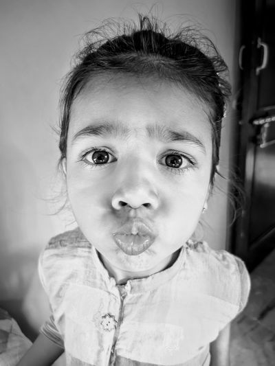 Portrait of cute girl making faces at home