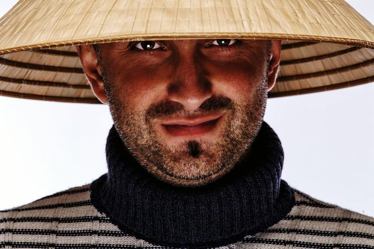 Portrait Of Mid Adult Man Wearing Asian Style Conical Hat Against White Background