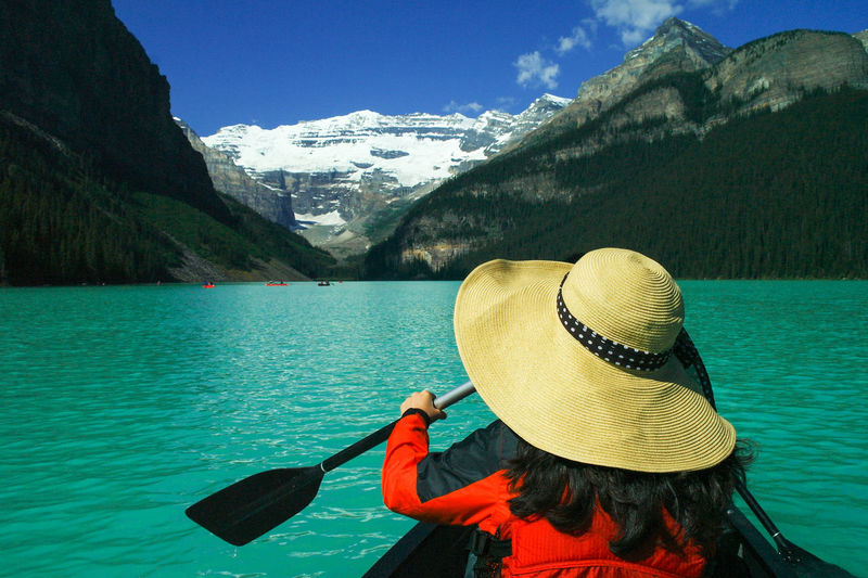 Rear View Of Woman Wearing Hat Canoeing On Lake