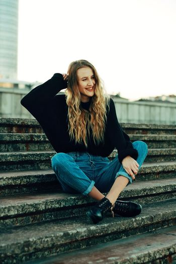 Portrait of smiling young woman sitting on steps in city against sky