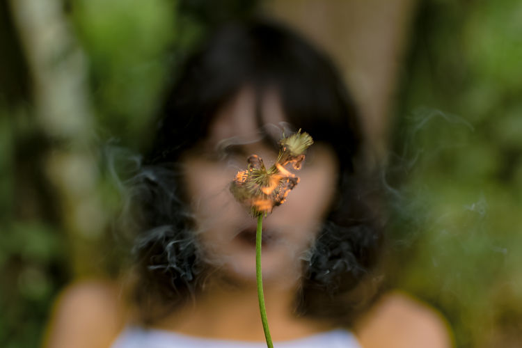 Young Woman With Burning Dandelion Against Trees