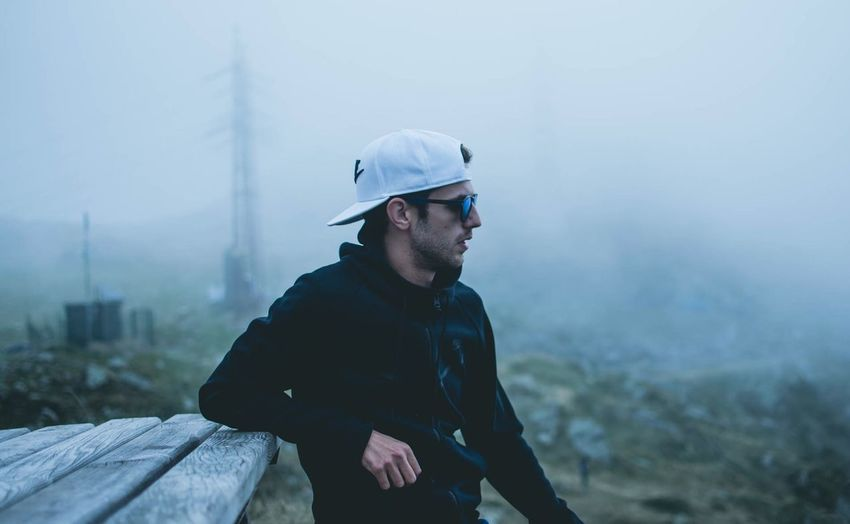 Young man looking away in foggy weather