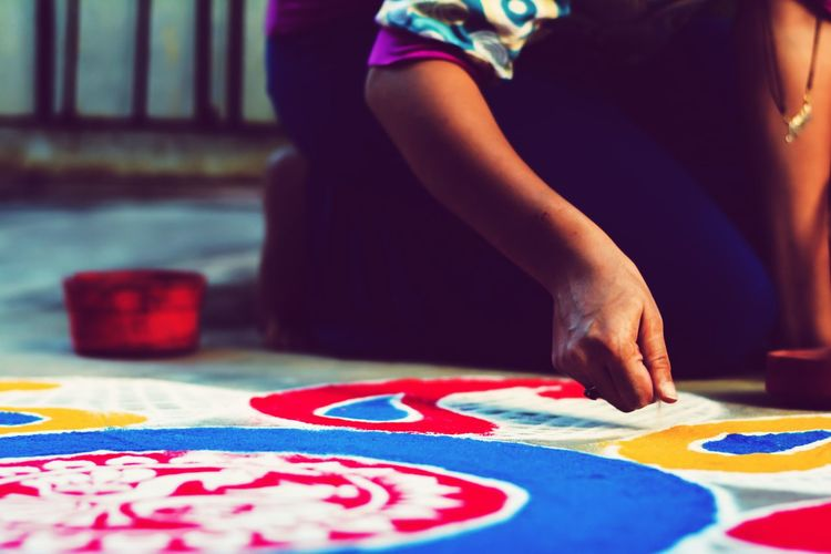 Midsection Of Woman Making Colorful Rangoli