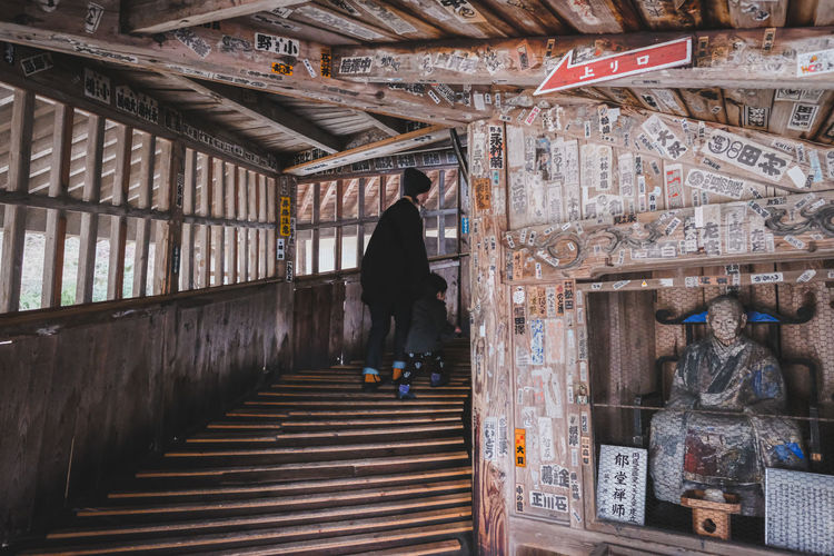 Rear view of man walking on staircase in building