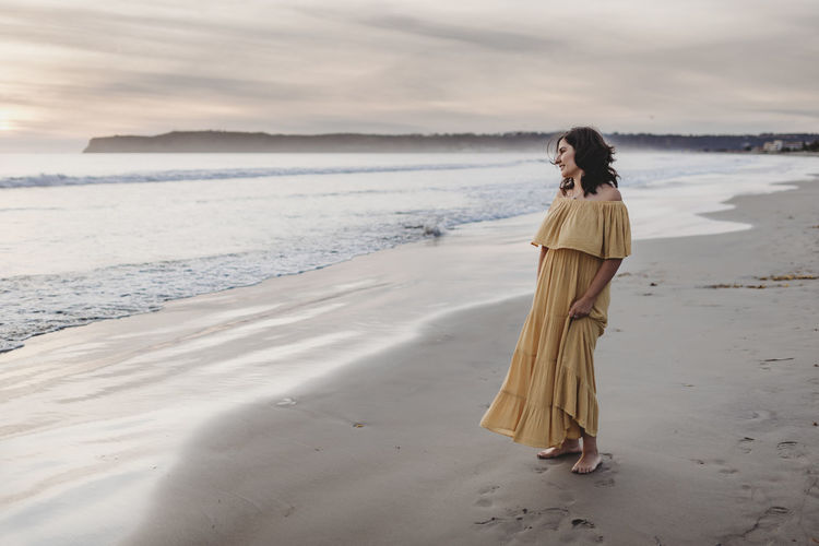 Woman standing on beach by sea against sky