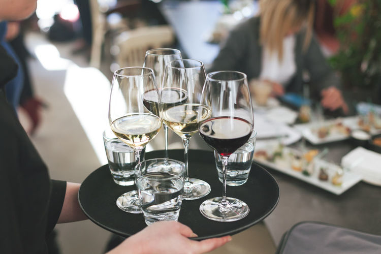 waitress at restaurant serving white and red wine Champagne Event Toast Waitress Alcohol Bar Catering Celebrate Celebration Day Drink Drinking Glass Food And Drink Hand Holding Indoors  People Plate Real People Refreshment Restaurant Serving Table Wine Wineglass