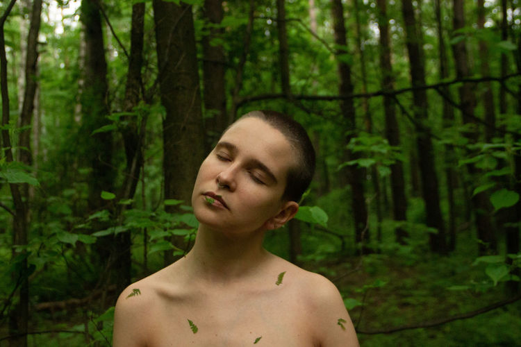 Portrait of shirtless man in forest