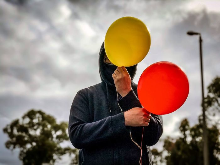 Person holding red and yellow balloons against sky.