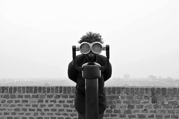 Portrait of man looking through coin-operated binoculars at observation point