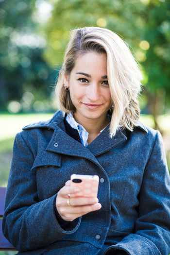 Portrait of beautiful young woman using smart phone at outdoors. Adult Blond Hair Close-up Communication Connection Day Focus On Foreground Front View Holding Lifestyles Mobile Phone One Person Outdoors Park - Man Made Space Portable Information Device Portrait Real People Smart Phone Smiling Technology Text Messaging Using Phone Wireless Technology Women Young Adult