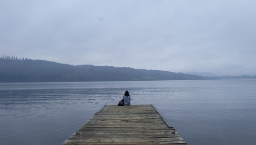 Rear view of woman sitting on pier lake against sky