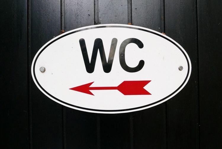 Close-up of restroom sign on door