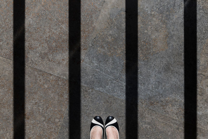 Low section of woman on marble flooring with shadow of prisoner bars
