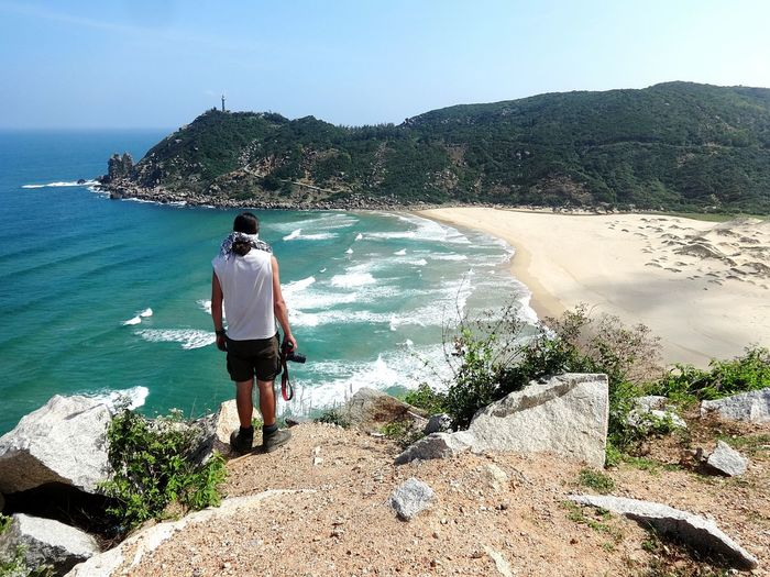 Rear view of man holding camera while standing on rock overlooking beach