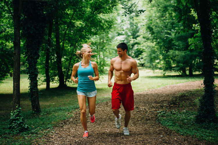 Full Length Of Couple Jogging On Field